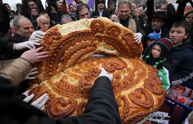 People gather to receive a piece of traditional Christmas bread in Belgrade
